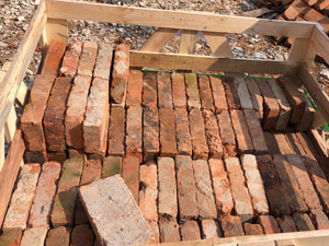 Red reclaimed bricks packed into the crate